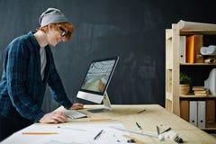 Arquitecto joven sonriente en el lugar de trabajo fotos de archivo libres de regalías