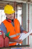 Arquitecto Looking At Blueprint en sitio Fotografía de archivo libre de regalías