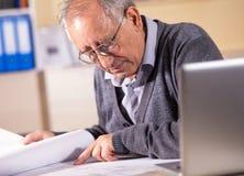 Arquitecto mayor que trabaja en modelo de la construcción en oficina foto de archivo libre de regalías