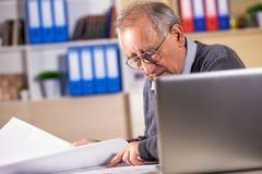 Arquitecto mayor que trabaja en modelo de la construcción en oficina imagenes de archivo