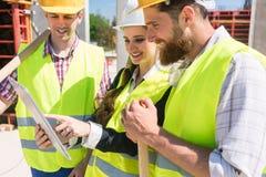 Arquitecto o encargado que muestra el plan electrónico del edificio fotografía de archivo