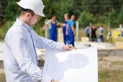 Arquitecto o ingeniero que comprueba planes en sitio imagen de archivo