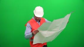 Arquitecto que comprueba dibujos de construcción técnicos en fondo verde almacen de video