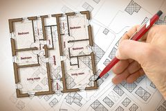 Arquitecto que dibuja un edificio residencial sobre un mapa catastral imaginario del territorio con los edificios, los campos y l imagen de archivo libre de regalías