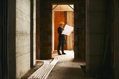 Arquitecto que se coloca en casa bajo construcción con la construcción del pla Fotos de archivo