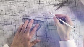 Arquitecto que toma medidas en plan arquitectónico de la construcción de viviendas del modelo con el lápiz, la regla, los comp almacen de video