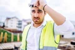 arquitecto que trabaja en emplazamiento de la obra, el casco que lleva y el chaleco de la seguridad foto de archivo libre de regalías