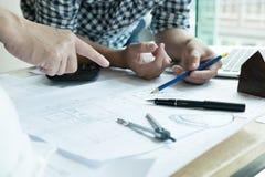 Arquitecto que trabaja en proyecto de las propiedades inmobiliarias con el socio en el workpla Fotografía de archivo libre de regalías
