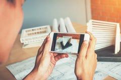 Arquitecto que usa el edificio modelo de la fotografía elegante del teléfono en oficina fotos de archivo