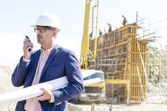 Arquitecto que usa el Walkietalkie mientras que se sostiene blueprints en el emplazamiento de la obra Imagenes de archivo