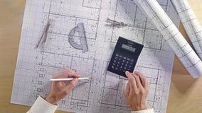 Arquitecto que usa la calculadora en plan arquitectónico de la construcción de viviendas del modelo con el lápiz, la regla, los c metrajes
