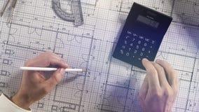 Arquitecto que usa la calculadora en plan arquitectónico de la construcción de viviendas del modelo con el lápiz, la regla, los c almacen de video