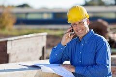 Arquitecto sonriente Using Mobile Phone en el sitio Imagenes de archivo