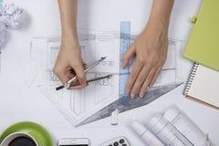 Arquitecto Working On Blueprint Lugar de trabajo de los arquitectos - proyecto arquitectónico, modelos, regla, calculadora, orden Imagen de archivo libre de regalías