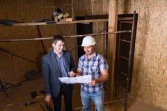 Arquitecto y capataz Inspecting Building Plans Foto de archivo libre de regalías