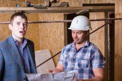 Arquitecto y capataz Inspecting Building Plans Foto de archivo