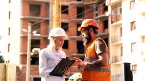 Arquitecto y constructor en el emplazamiento de la obra El ingeniero de la mujer y el constructor brutal comunican el fondo del e almacen de metraje de vídeo