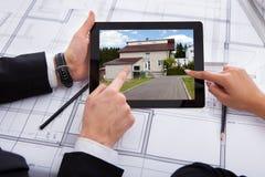 Arquitectos con la tableta digital que mira la casa Foto de archivo libre de regalías