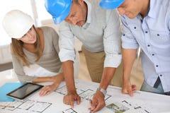 Arquitectos con los cascos que trabajan en oficina Imagen de archivo