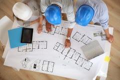 Arquitectos con los cascos que trabajan junto Foto de archivo