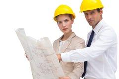 Arquitectos con plan de la construcción y los cascos amarillos Fotografía de archivo