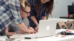 Arquitectos jovenes que comprueban medidas del dibujo con el divisor imagen de archivo