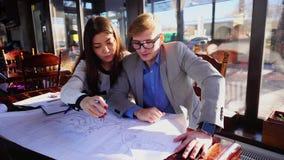 Arquitectos jovenes que crean nuevo proyecto en el café almacen de metraje de vídeo