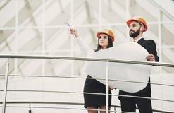 Arquitectos profesionales contentos positivos que miran para arriba mientras que habla del proyecto Imagen de archivo libre de regalías
