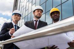 Arquitectos profesionales en los cascos que trabajan con el modelo fuera del edificio moderno Imagen de archivo libre de regalías
