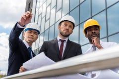 Arquitectos profesionales en los cascos que trabajan con el modelo fuera del edificio moderno Fotografía de archivo