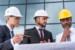 Arquitectos profesionales en los cascos que trabajan con el modelo fuera del edificio moderno Imágenes de archivo libres de regalías