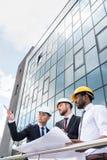 Arquitectos profesionales en los cascos que trabajan con el modelo fuera del edificio moderno Fotografía de archivo libre de regalías