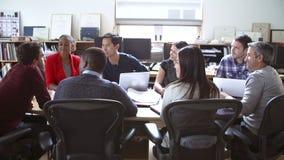 Arquitectos que se sientan alrededor de la tabla que tiene reunión almacen de video
