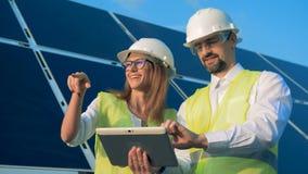 Arquitectos que trabajan en una tableta cerca de los módulos solares almacen de metraje de vídeo