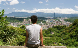 A arquitectura da cidade bonita com um homem senta e presta atenção distante á Foto de Stock