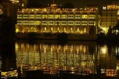 Arquitectura en el banco del lago con la reflación en el agua en noche fotografía de archivo