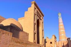 Arquitectura tradicional dentro de la ciudad vieja de Khiva con el alminar de Khodja del Islam en el fondo, Khiva imagen de archivo libre de regalías