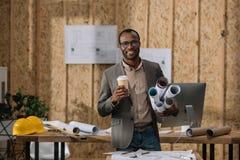 arquiteto afro-americano do smilign com o café a ir e os modelos rolados foto de stock royalty free