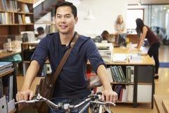 Arquiteto Arrives At Work na bicicleta que empurra o através do escritório Fotografia de Stock Royalty Free