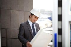 Arquiteto asiático novo que verifica o plano Imagens de Stock Royalty Free
