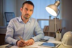 Arquiteto atrativo novo que trabalha tarde no escritório foto de stock royalty free