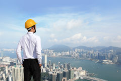 Arquiteto com o capacete que olha a construção da cidade Fotos de Stock Royalty Free