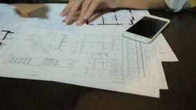 Arquiteto da mulher que trabalha com folhas, disposições e desenhos do modelo dos locais vídeos de arquivo