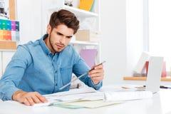 Arquiteto do homem novo que guarda a régua sobre o diagrama na mesa Imagem de Stock