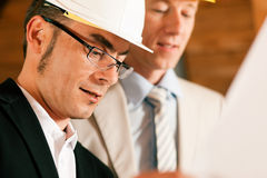Arquiteto e coordenador de construção que discute plantas imagem de stock