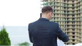 Arquiteto empreendedor que fala no telefone ao estar ao lado da construção nova filme