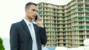 Arquiteto empreendedor que fala no telefone ao estar ao lado da construção nova video estoque
