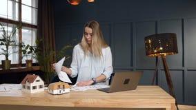 Arquiteto fêmea focalizado que trabalha no desing da casa futura usando o modelo, o modelo da casa e o portátil filme