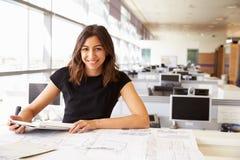 Arquiteto fêmea novo que trabalha com computador e modelos Foto de Stock Royalty Free