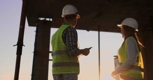 Arquiteto f?mea e trabalhador da constru??o que agitam as m?os Opinião de baixo ângulo, espaço da cópia filme